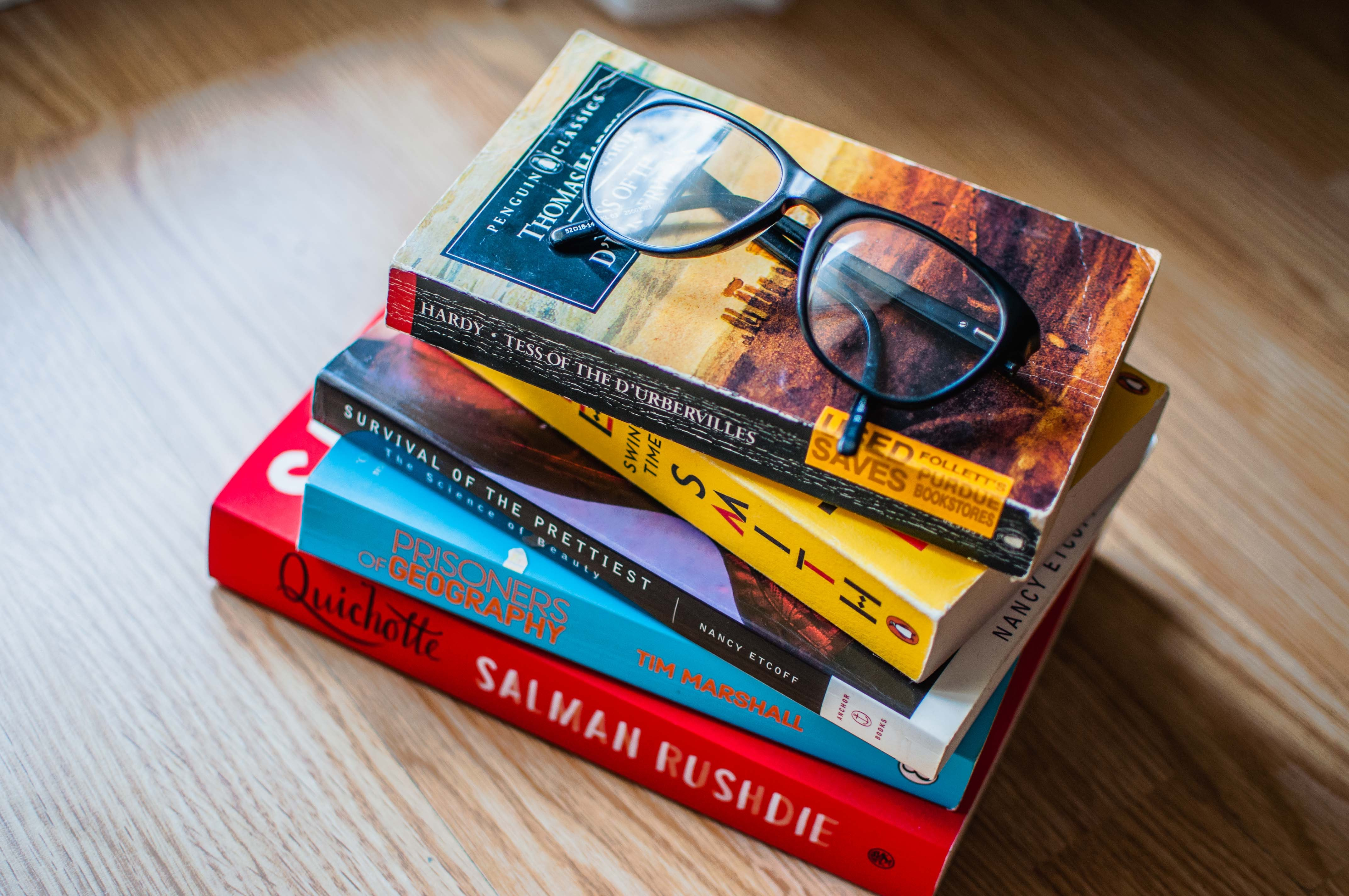 stack of books from around the world with reading glasses on top from localbini biniblog local travel experiences quarantine home